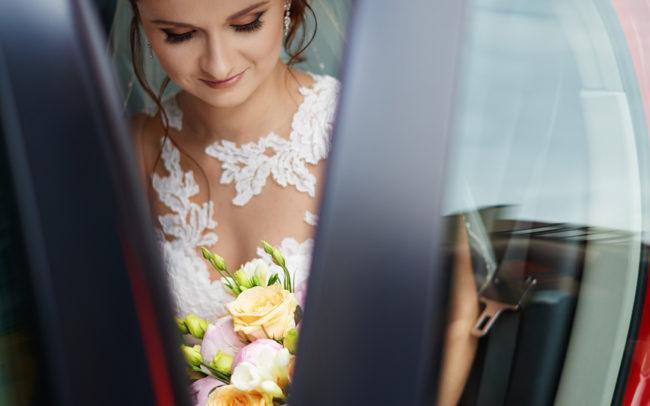 Zdjęcie panny młodej w aucie z wiązanką.